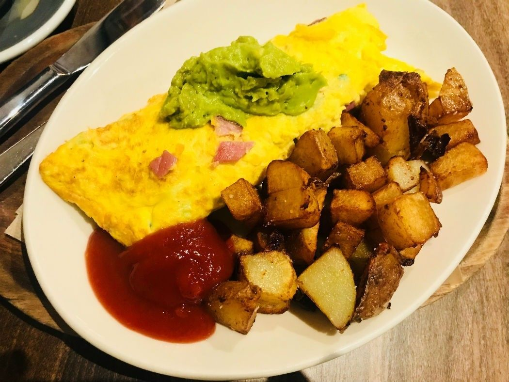 omelette with guacamole and diced potatoes and red sauce on a plate