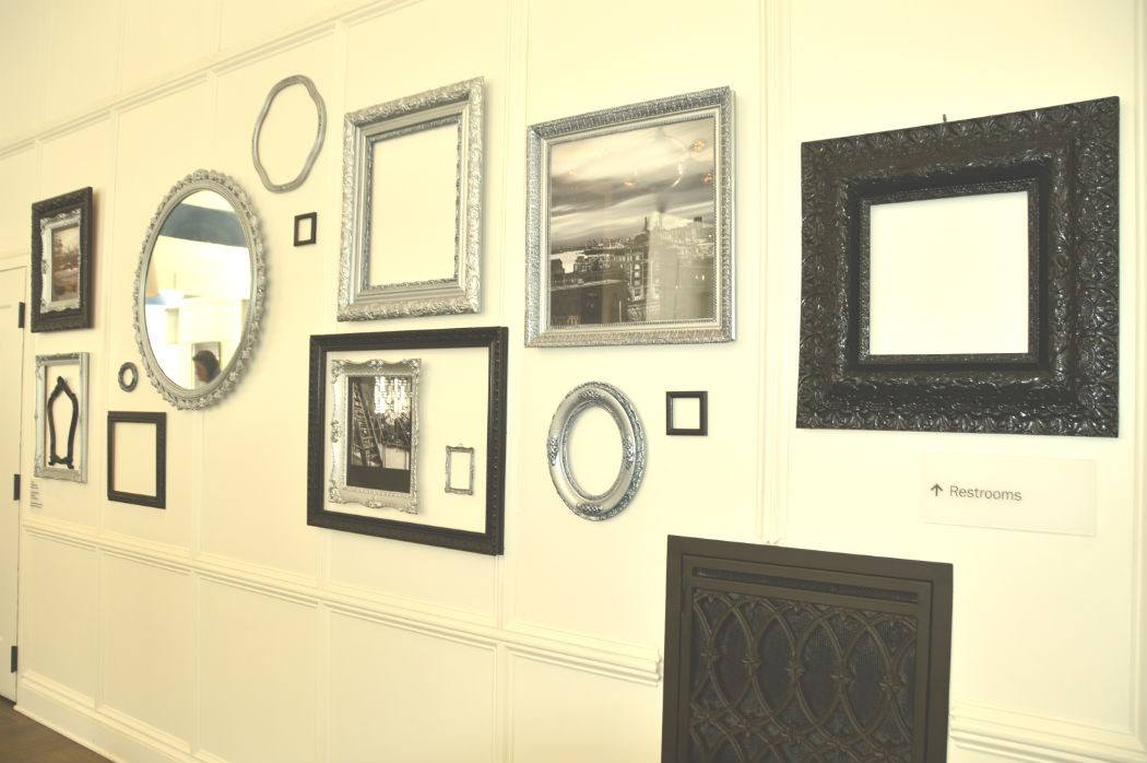 A mix of mirrors and images with black and silver frames on a white wall