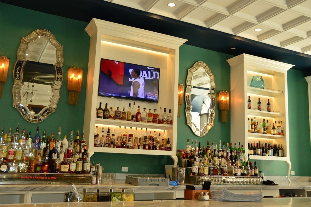 hotel indigo bar with tv, mirror and bottles of alcohol on display