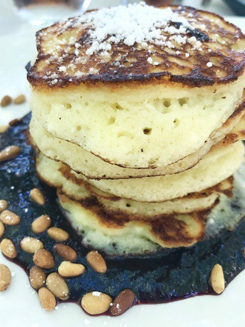 stack of pancakes with blueberry sauce and pinenuts