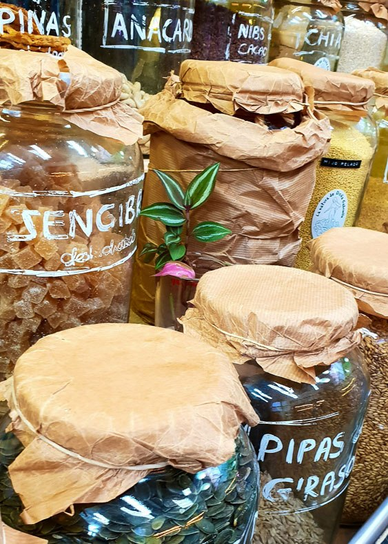 Glass jars with seeds and nuts inside on display at a market