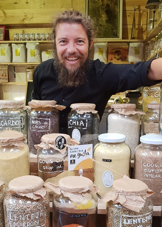 bearded man with glass jars of spices in a market