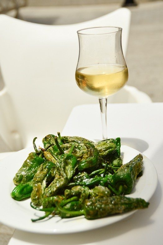 plate of padron peppers and glass of white wine