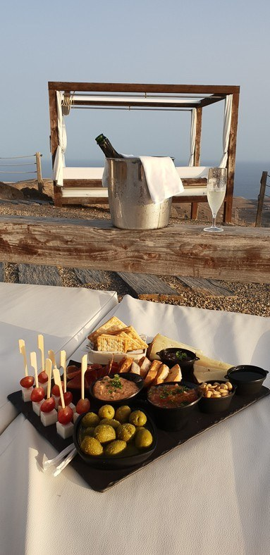 plate of snacks, bottle of wine in a bucket and a sun bed at Salobre resort gran canaria
