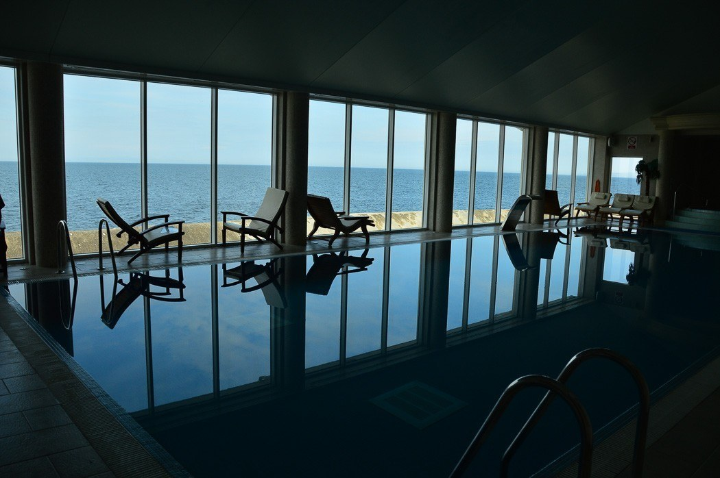 spa inside pool with lounge seats and a view of the sea