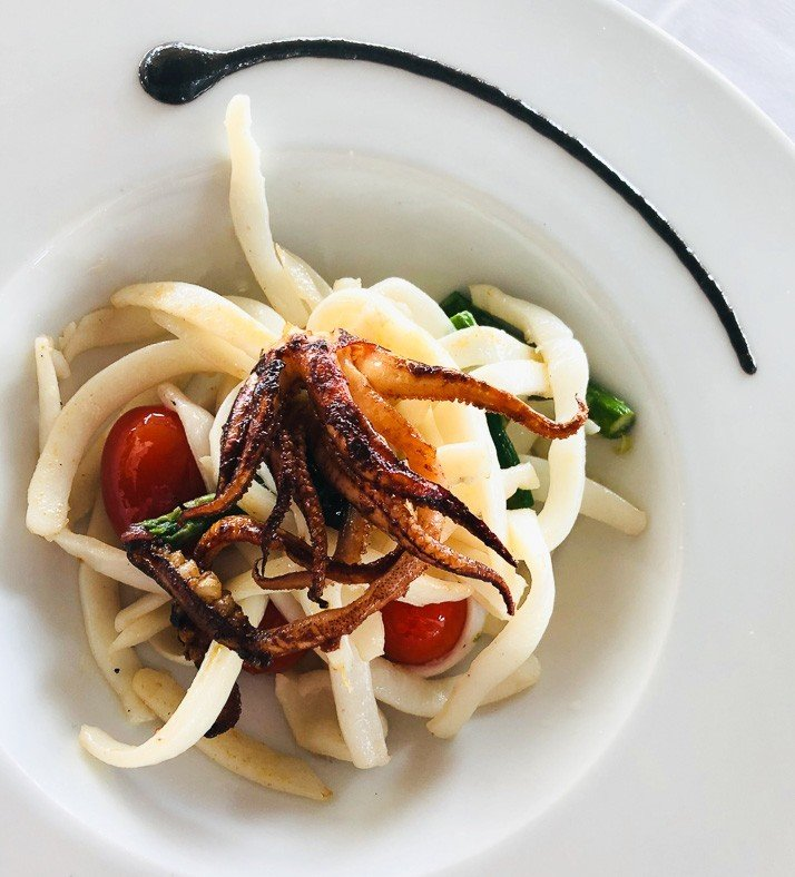 Grilled calamari on a white plate