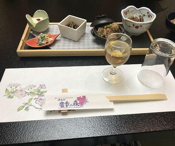 typical japanese meal with multiple dishes, a glass of sake and chopsticks