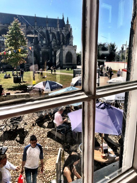 view of exeter cathedral looking out the window of Tea on the Green Cafe