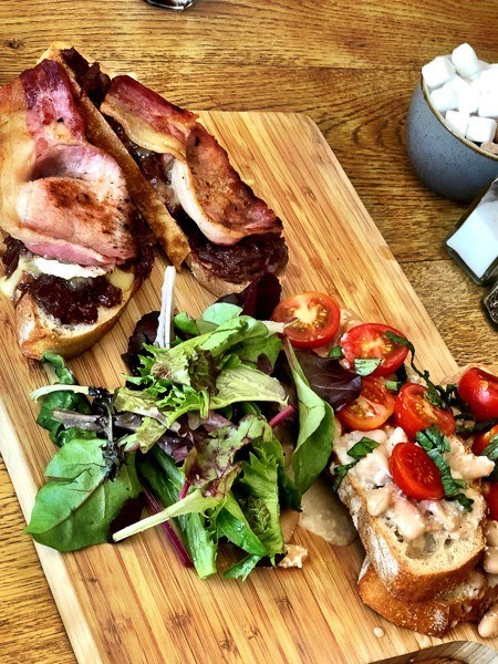 open sandwiches with bacon, tomatoes and lettuce on a wooden board