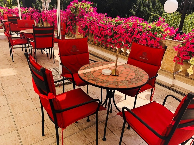 outside tables with red chairs at Hotel Imperial Frantiskovy Lazne