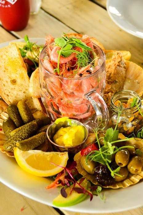 prawns in a glass mug with bread, lemon, olives and more