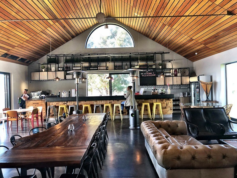 inside a modern winery in stellenbosch with a comfortable couch and big table