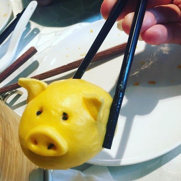 hong kong dumpling shaped like pig held between chopsticks