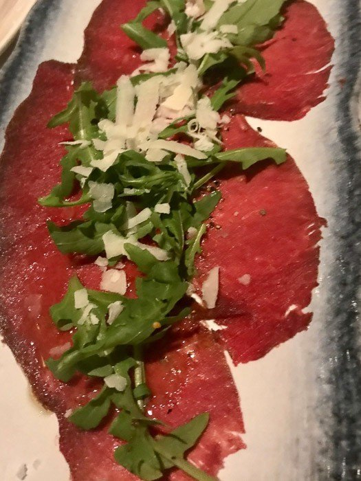 carpaccio with rocket and parmesan on plate at Hotel Ranga Iceland