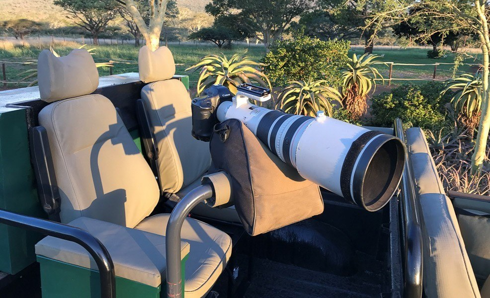 large camera lens on a beanbag in a safari vehicle
