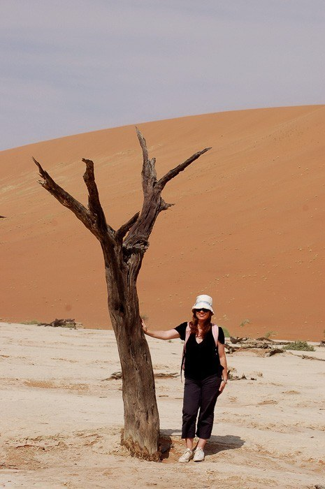 woman stands with arm on bare tree in dead vlei namibia