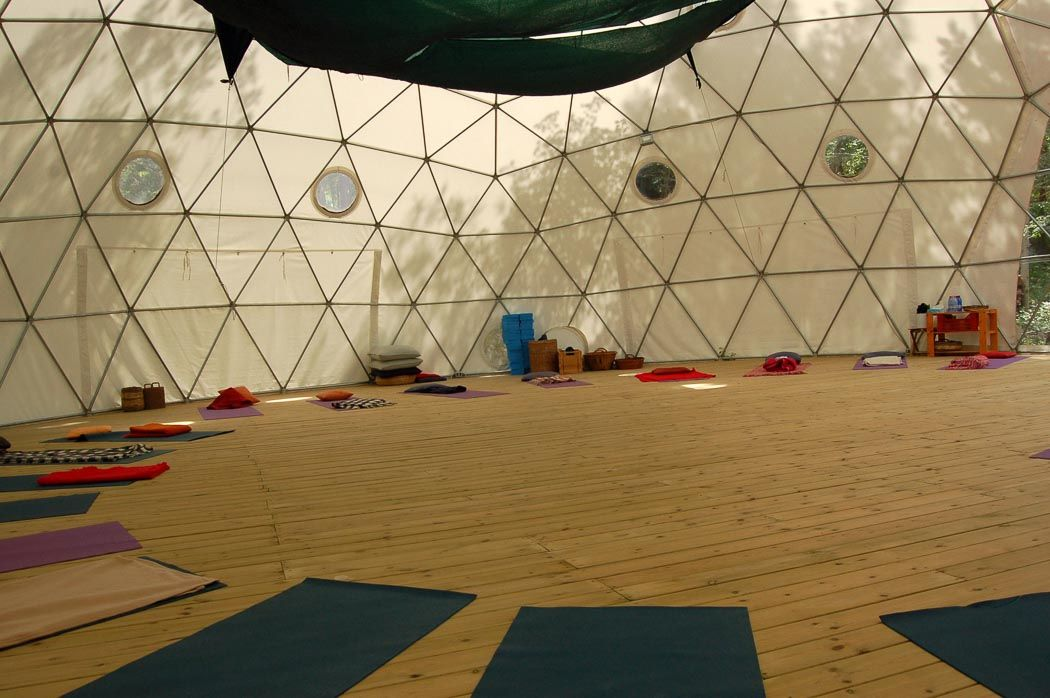inside a yurt with floorboards and yoga mats