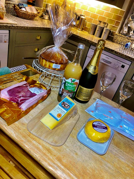 food and drinks on a wooden table in Bruern cottage - welcome pack