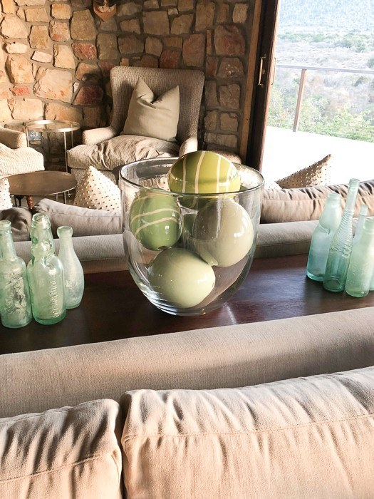 green ostrich eggs in a clear vase in a living room area at Kwandwe
