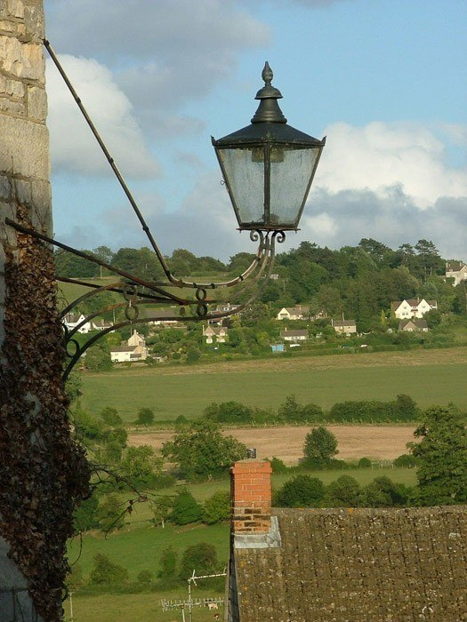 old fashioned street light with cotswolds greenery behind