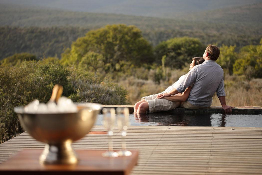 couple relaxing on the edge of an infinity pool on a safari honeymoon