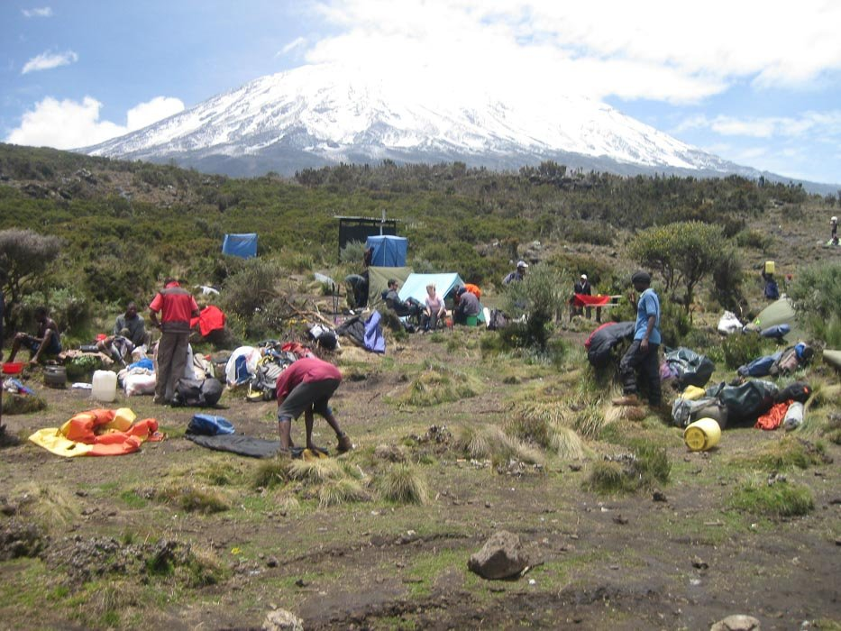 people setting up camp with the top of mount kilimanjaro in the background