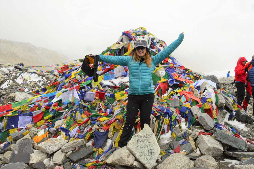 woman in jacket with hands up in front of prayer flags pile mount everest base camp