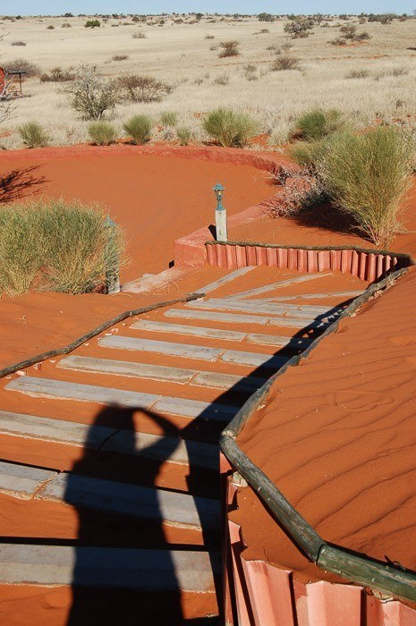 red sands with a path and shadow of person taking photo in namibia