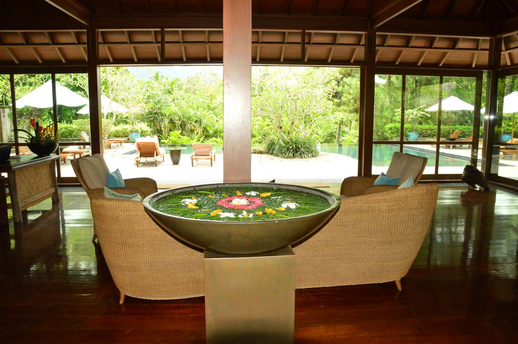 table with large bowl and flowers and pool in background