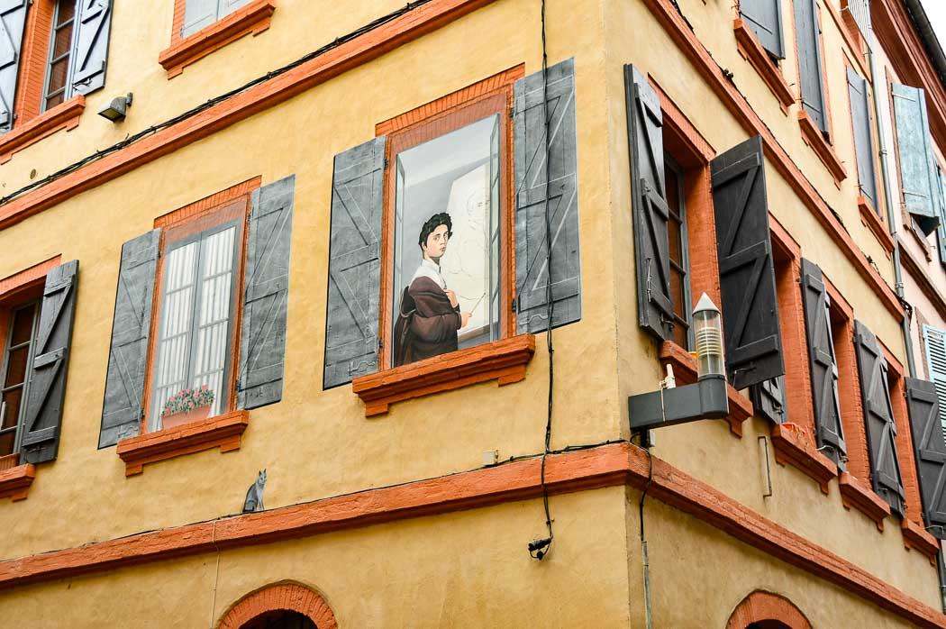 building with painted shutters and person in Montauban