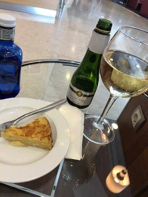 plate with tortilla glass of wine on a table in the iberia business class lounge