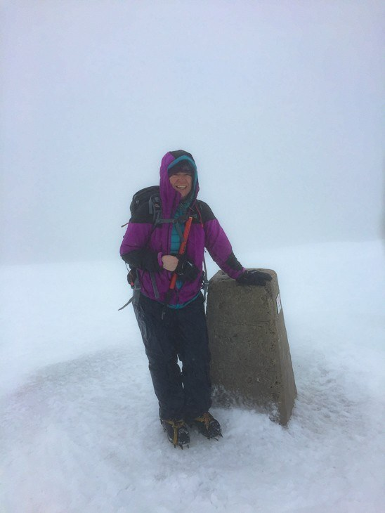 woman hiker at top of Ben Nevis in white out conditions