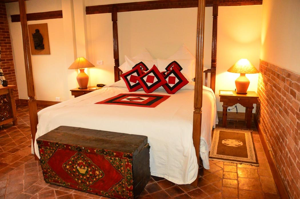 bedroom with poster bed and side tables at dwarika's kathmandu hotel