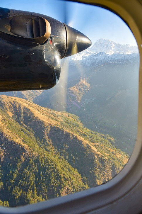 looking out of a plane window onto a propellor and the himalayas on the way to Lukla nepal