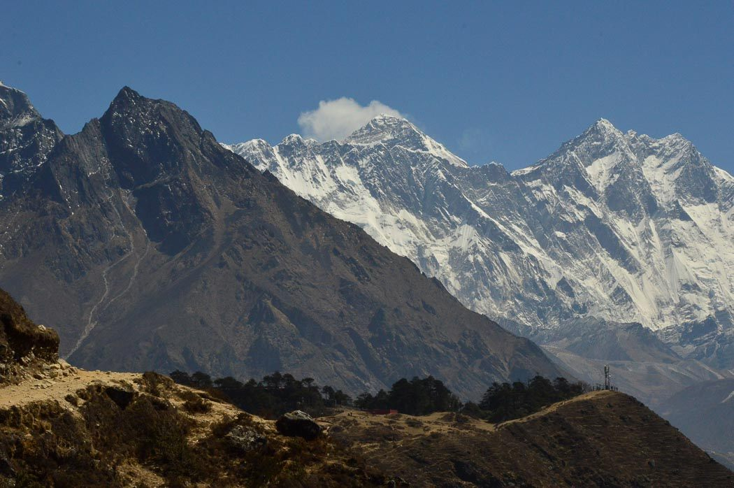 the himalaya mountains with everest in the middle and a cloud on top