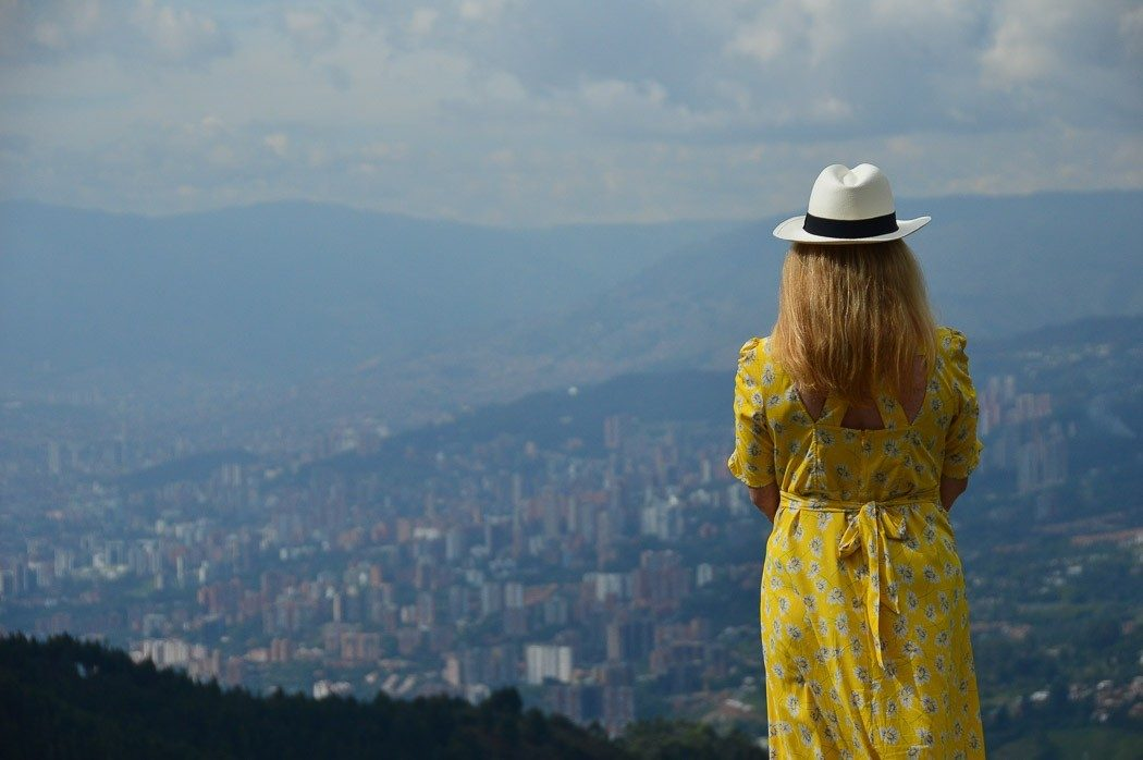woman in yellow dress look over medellin