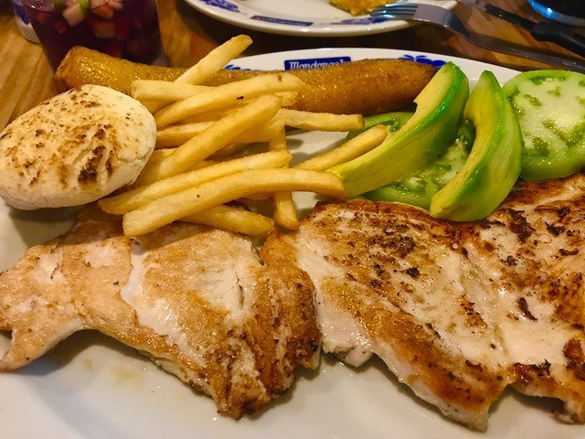 grilled chicken, chips and avocado on a plate