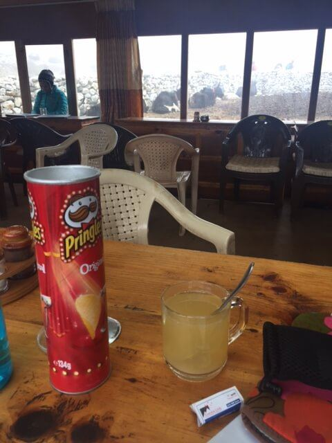 tin of pringles and a ginger lemon and honey drink on a wooden table in a tea house on the way to everest base camp
