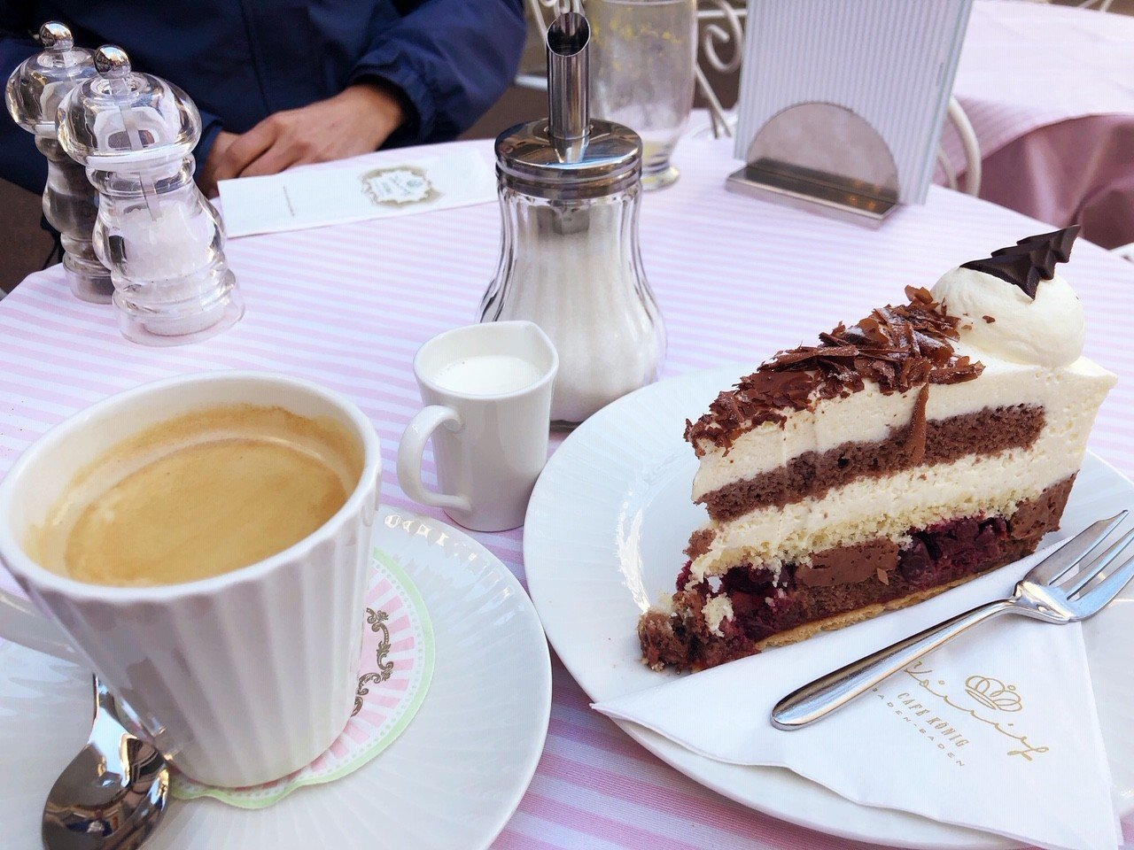 coffee and slice of black forest cake set on a pink table at Cafe Koenig