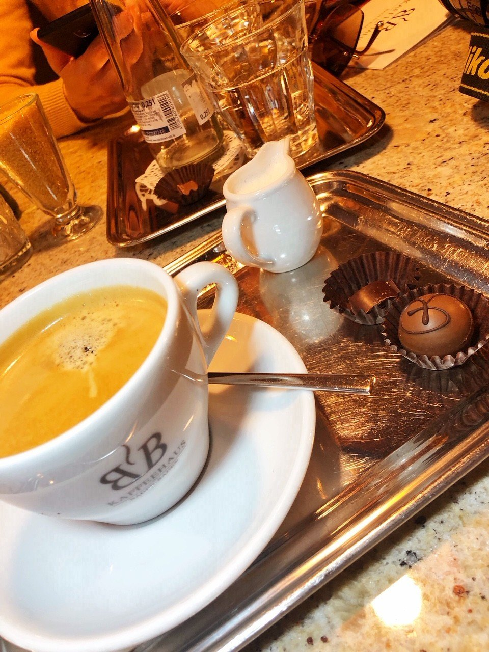 white cup of coffee and saucer on silver tray with milk and chocolates