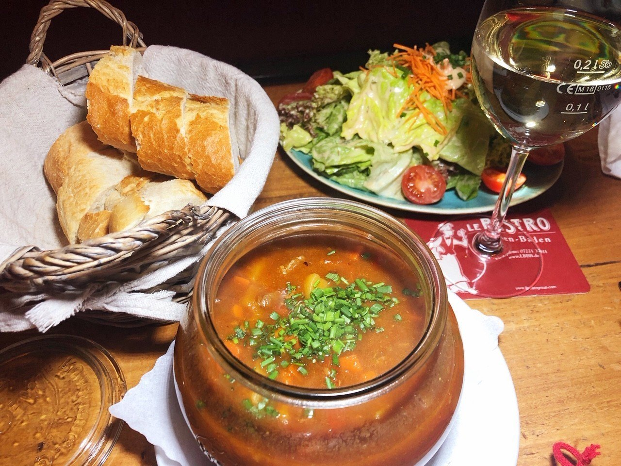 goulash soup with bread, salad and wine at le-bistro-baden-baden