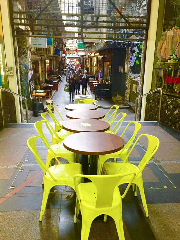 tables with yellow chairs in melbourne laneway