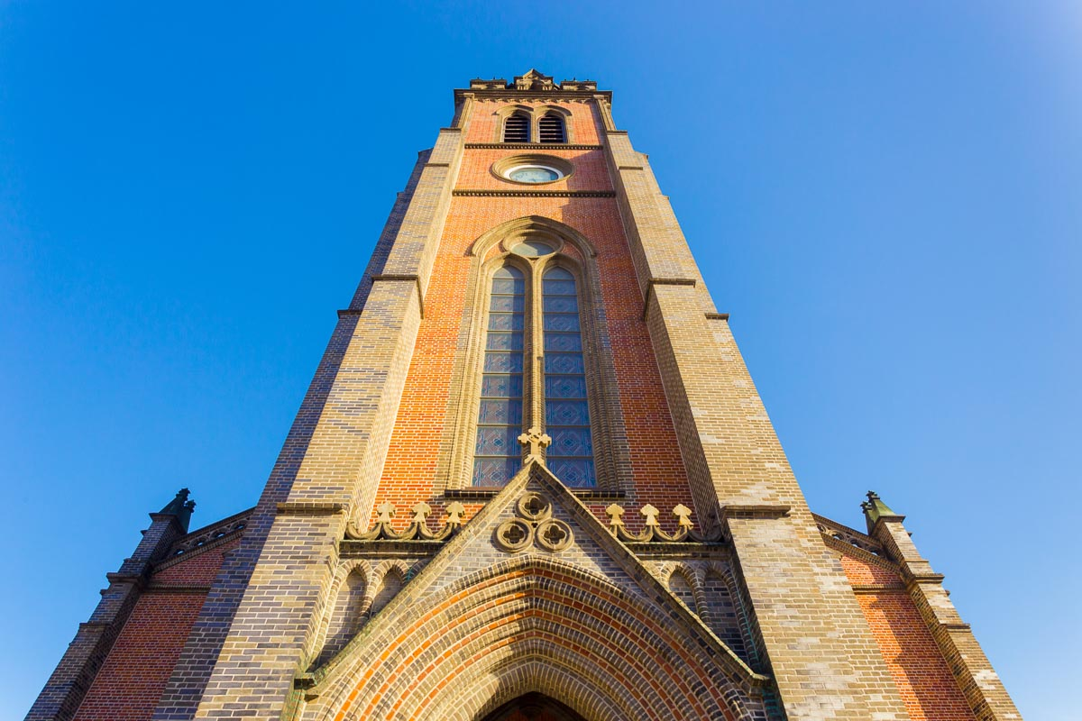 Low angle view of front of brick steeple of the Myeongdong Cathedral on a clear, blue sky day in Seoul, South korea