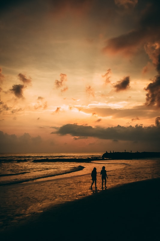couple walking on the beach at sunset in canggu bali