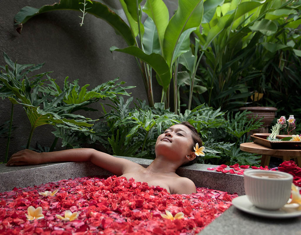 woman in rose petal bath at Komea resort bali indonesia