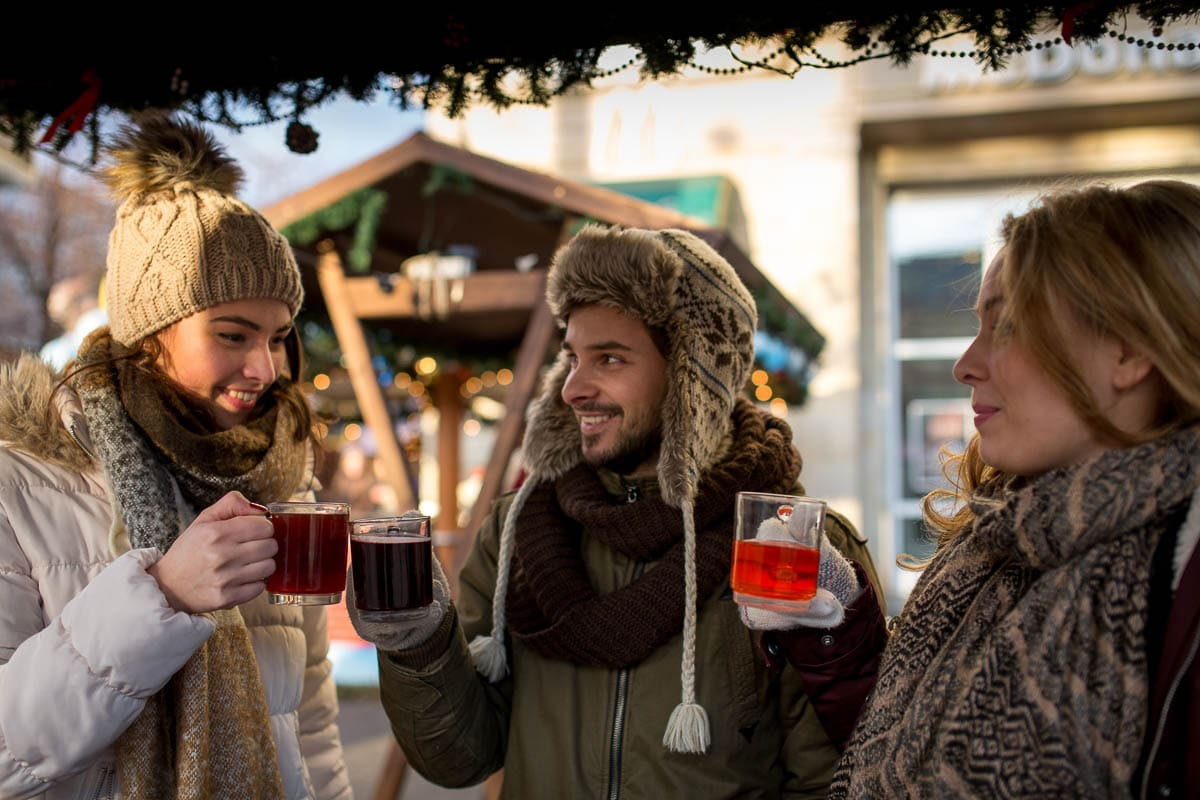 3 people in warm weather gear toasting with drinks