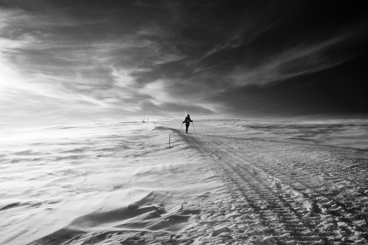 figure of person in distance on a snowy plain in black and white