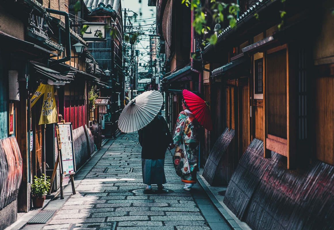 geishas with umbrellas in kyoto