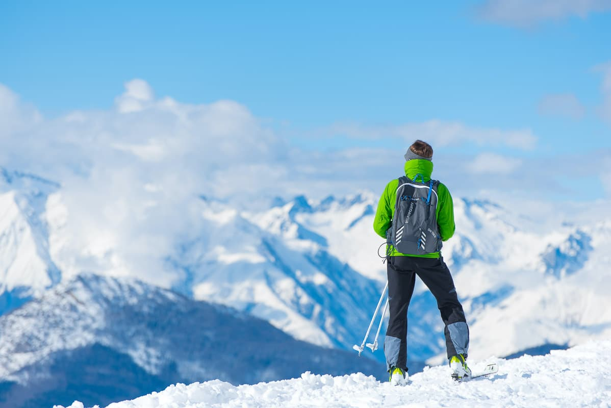 solo skier in green jacket looking over snowy mountains
