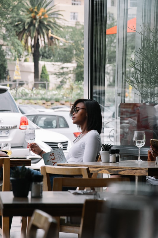woman in cafe reading newspaper